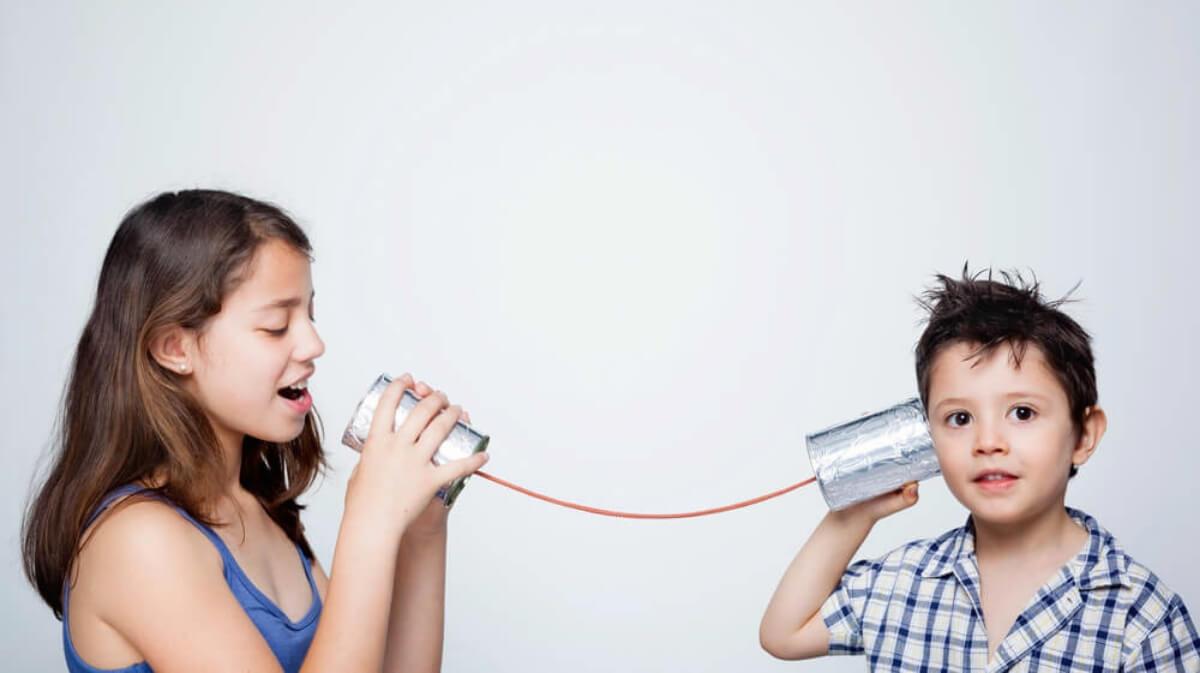 duas crianças brincando de telefone sem fio