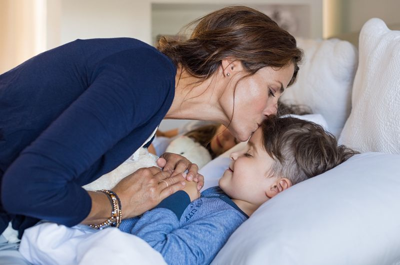 mãe dando beijo de boa noite no filho