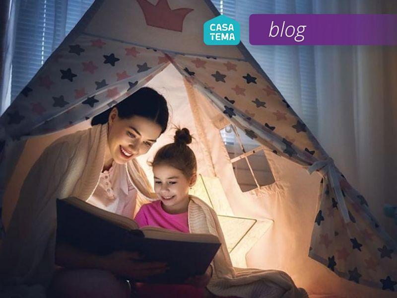 Mamãe e filha lendo histórias infantis na tenda infantil