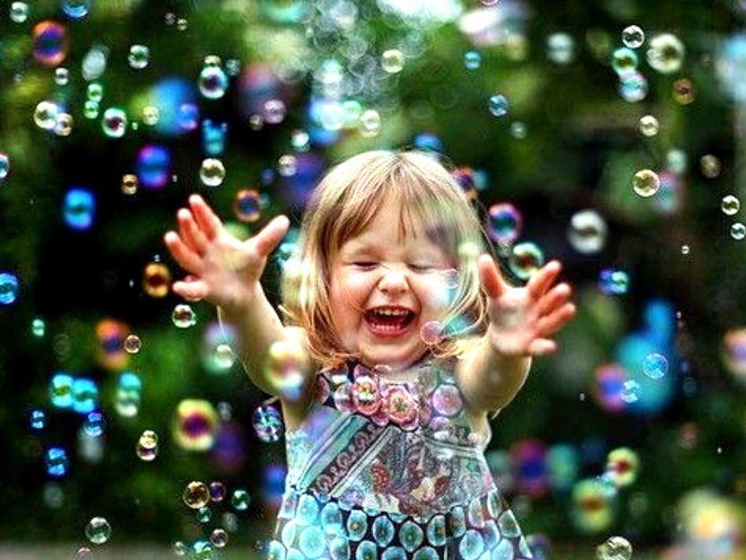 menina sorrindo com bolhas de sabão no ar