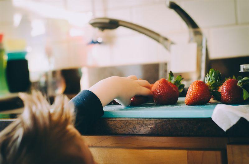 criança pegando morango