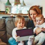 Mãe com duas crianças no colo olhando para o tablet