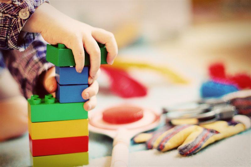 Mão de criança segurando brinquedo