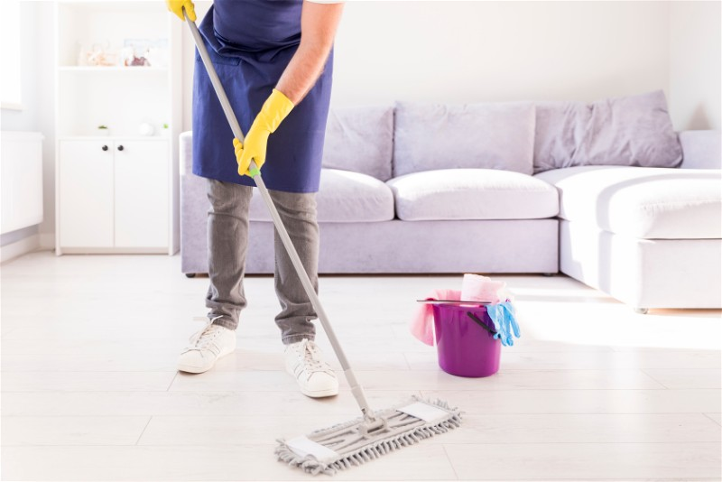 Pessoa limpando sala de uma casa