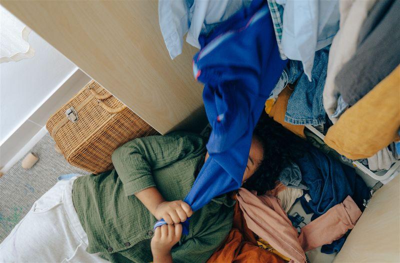 Criança deita no meio de um monte de roupas caindo do guarda-roupa