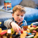 Menino com vários brinquedos jogados sobre a mesa