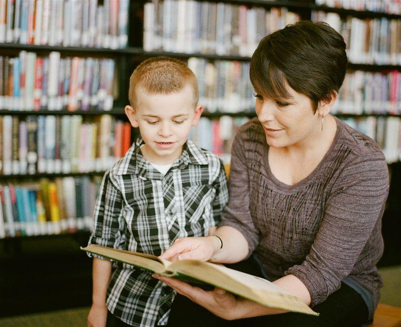 Mãe com livro lendo para seu filho