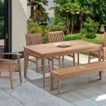 Imagem de uma mesa com quatro cadeiras e um banco comprido