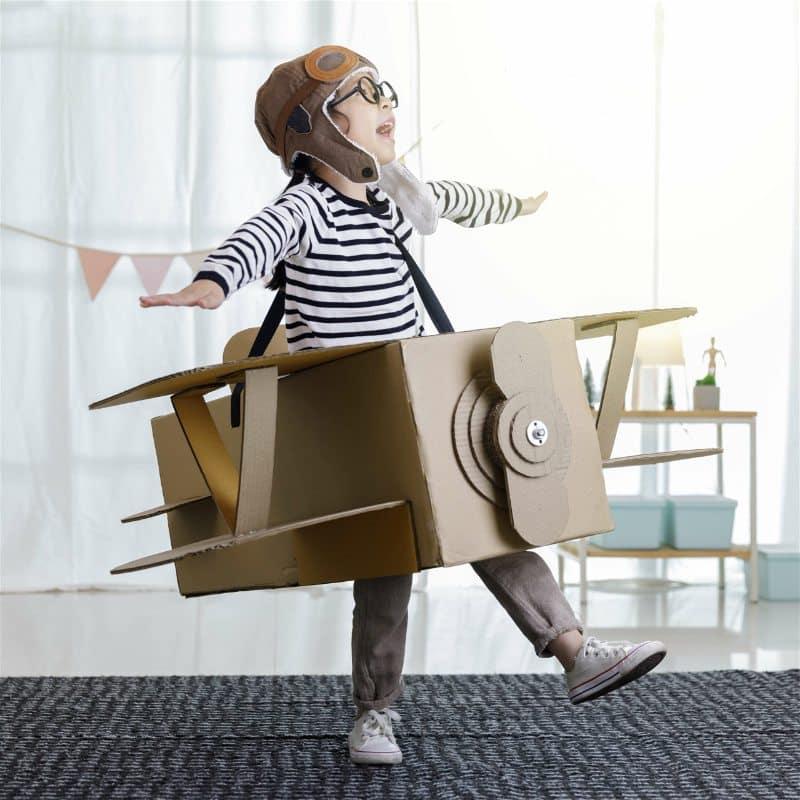 criança brincando com avião de papelão