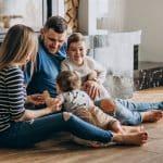 família sentada no chão de casa