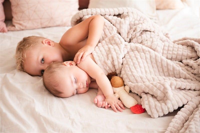 criança dormindo com irmão mais novo