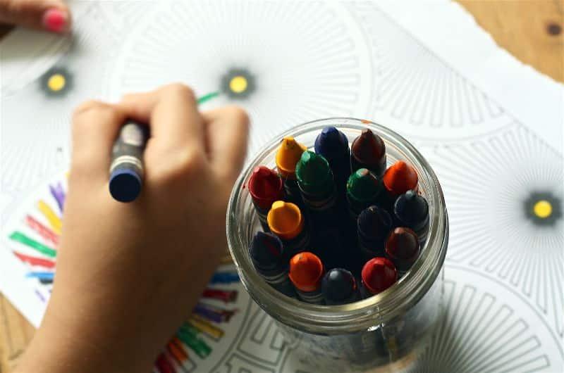 crianca desenhando com giz de cera